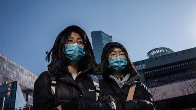 People wear protective masks as they walk outside a shopping mall in Beijing on January 23