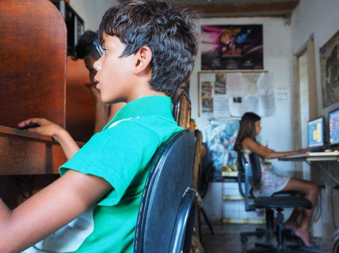 Brazil, 2015. A boy sits in an internet cafe.