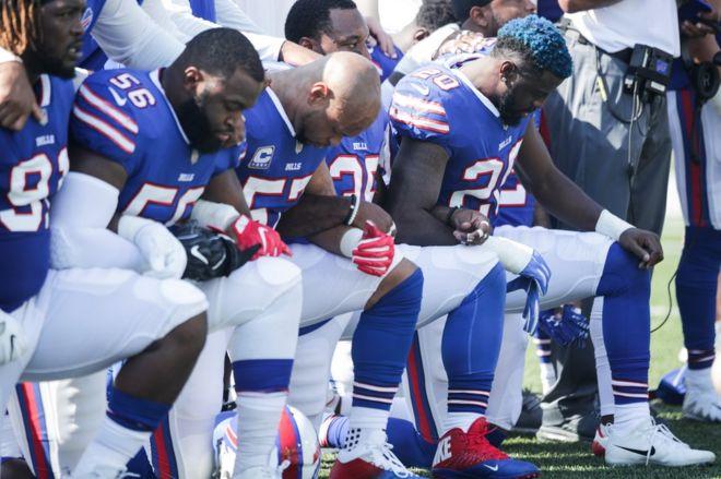 米アメフト試合前の国歌演奏で膝をつき黒人への暴力に抗議するデンバー・ブロンコスの選手たち(24日、ニューヨーク)