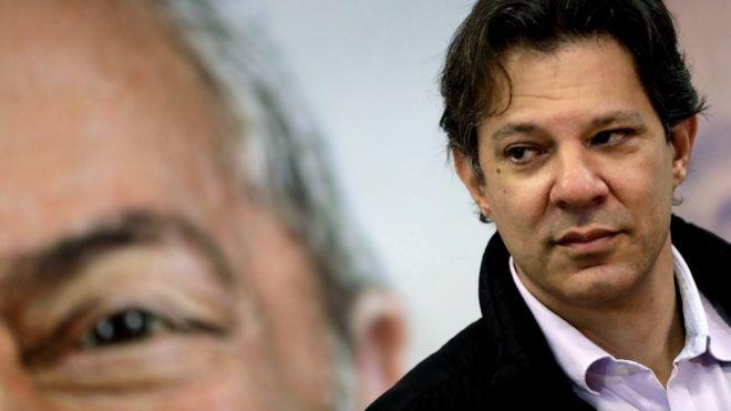 Haddad com imagem de Lula ao fundo
