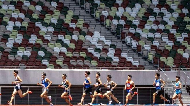 Hombres corriendo por un estadio.