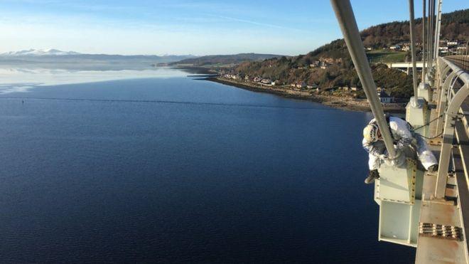 Un técnico trabajando sobre el puente Kessock, cerca de Inverness, con el Mar del Norte de fondo.