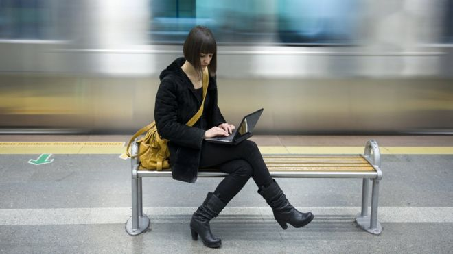 woman using laptop at train station
