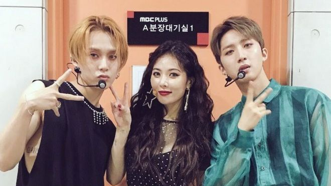 Three K-pop artists pose for a photo