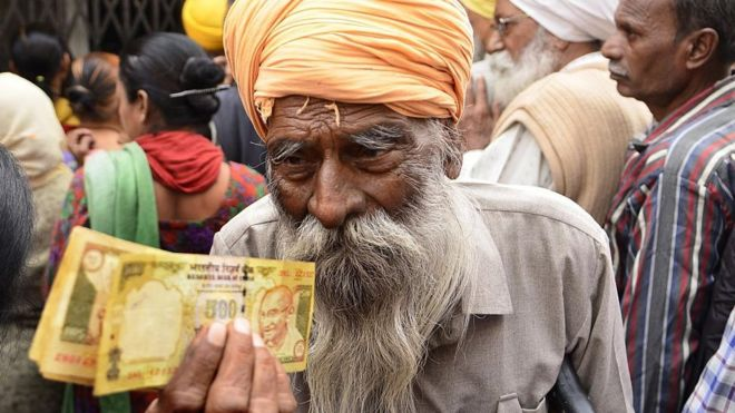 Man waits outside a bank to deposit and exchange 500 and 1000 rupee notes in Amritsar, India, in November 2016.
