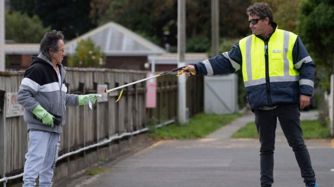 A man is given an appointment slip by a security guard using a stick outside a COVID-19 coronavirus clinic
