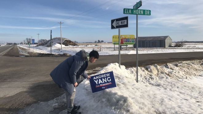 A Chinese student puts up a yard sign of presidential candidate Andrew Yang in Des Moines, Iowa.
