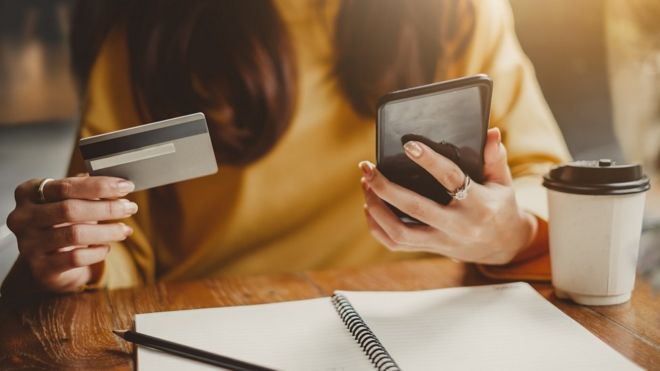Woman looking at mobile phone and credit card