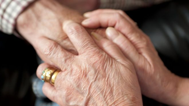 A dementia patient being comforted by a relative