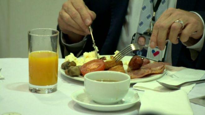 Мужчина в костюме ест жареный завтрак