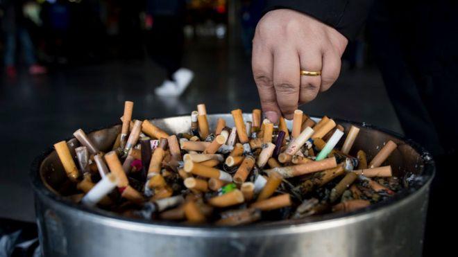 Un cenicero lleno de cigarrillos apagados.