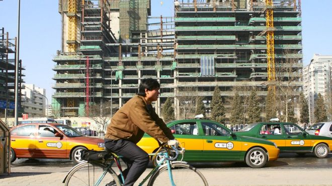 A man rides a bike past a construction site in China