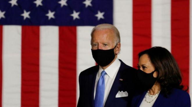 Biden e Harris de máscara em frente a bandeira americana