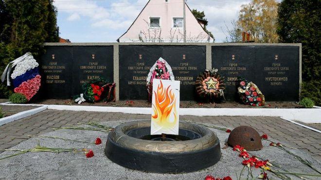 Изображение куска картона с нарисованным пламенем, прикрепленного к памятнику