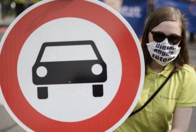 """Manifestante na Alemanha usa uma máscara com os dizeres: """"Emissões de combustível matam"""""""
