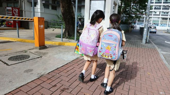 Children walk along a street in Hong Kong