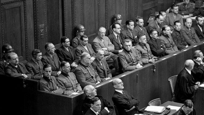 Немецкие врачи и ученые (23 человека) на скамье подсудимых во время Нюрнбергского процесса выслушивают предъявление им обвинений в бесчеловечных экспериментах над узниками нацистских концлагерей