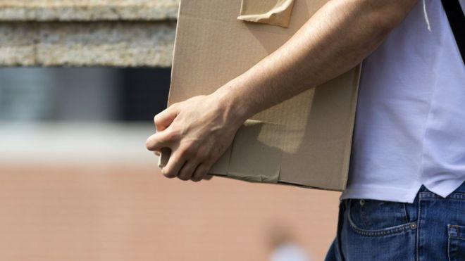 Homem demitido segura caixa com seus objetos