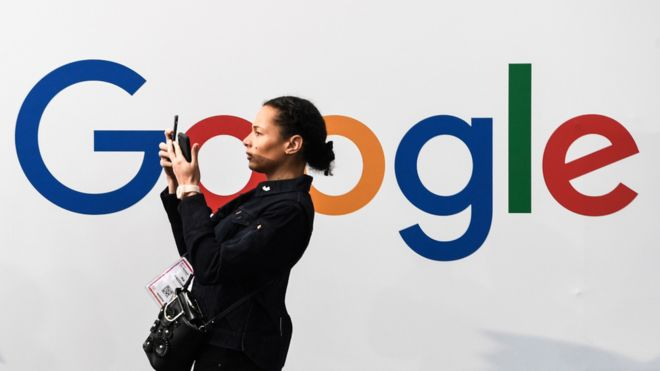 A woman uses her phone in front of a Google billboard