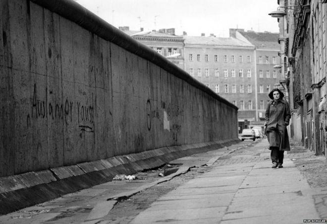 Woman walking alongside Berlin Wall, circa 1962-1968