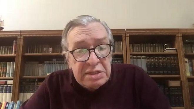 Olavo de Carvalho dá entrevista em frente a computador, com estante de livros atrás