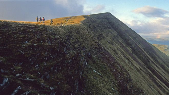 Walkers climbing up to the summit of Fan y Big