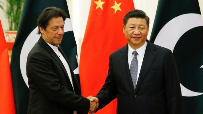 """China""""s President Xi Jinping (R) shakes hands with Pakistan""""s Prime Minister Imran Khan (L) ahead of their meeting at the Great Hall of the People in Beijing on November 2, 2018"""