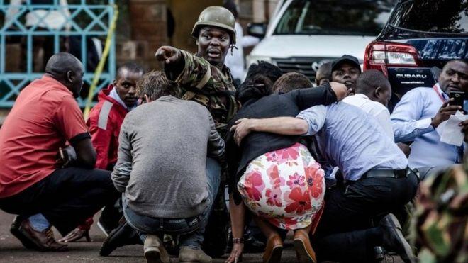 Un soldado da indicaciones entre personas que se protegen.