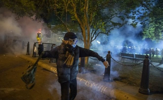 A protesters throws a stone at police (in the background) in Washington DC. Photo: 31 May 2020