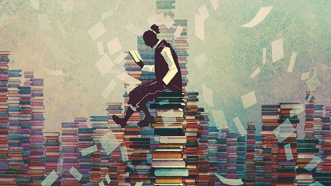 Alguien leyendo sobre pilas de libros