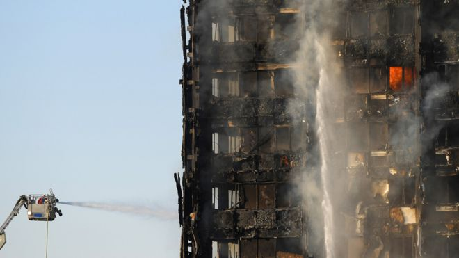 Firefighters continue their efforts to put out the fire, as daylight shows the complete destruction of Grenfell Tower