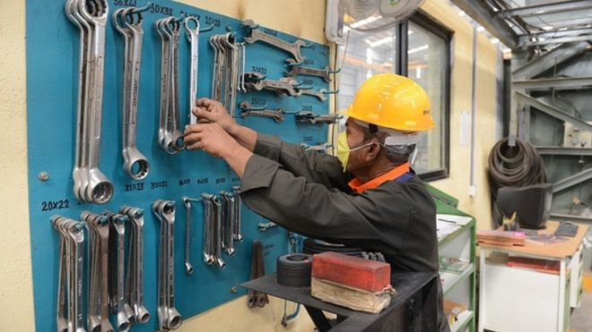 An Indian worker selects tools at a heavy fabrication manufacturing factory in Vasna Buzarg village