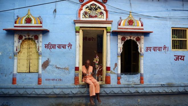 A priest sits in front of a Hindu temple