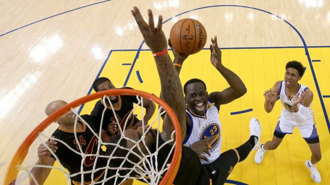 Draymond Green, de los Warriors, intenta anotar ante la oposición de J. R. Smith, de los Cavs.