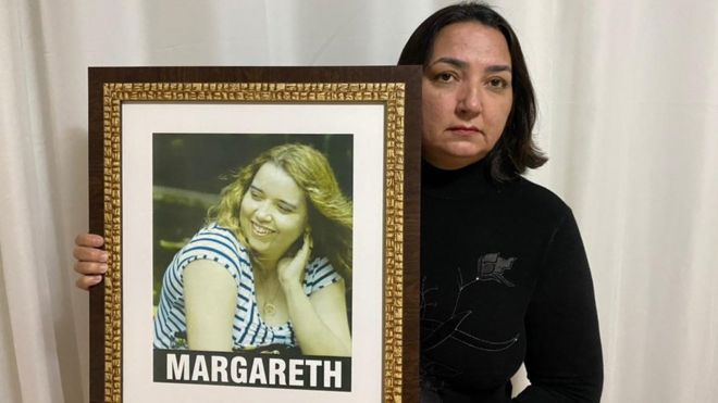 Ruth segura quadro com foto da irmã, Margareth, com olhar sério dentro da sala de casa