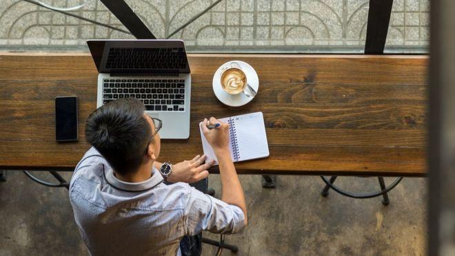 رجل أعمال شاب يدون ملاحظات إلى جانب جهاز كمبيوتر محمول على طاولة خشبية