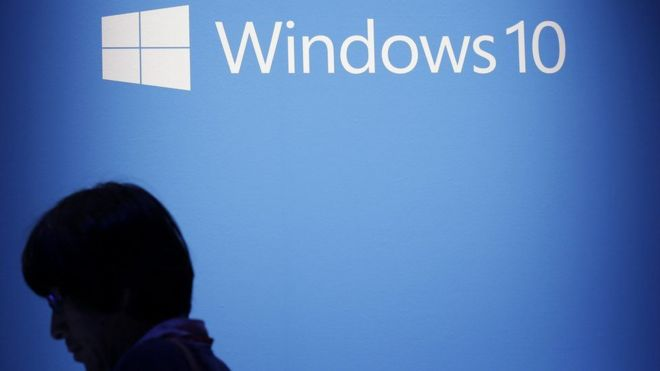 Logo de Windows 10 en una pantalla en la que aparece un señor.