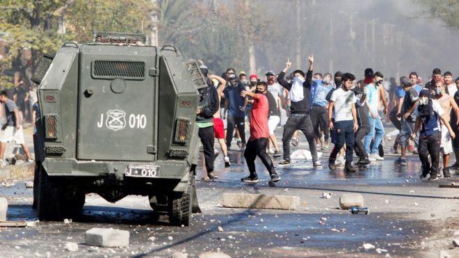 Manifestantes protestan frente a un camión de los carabineros.