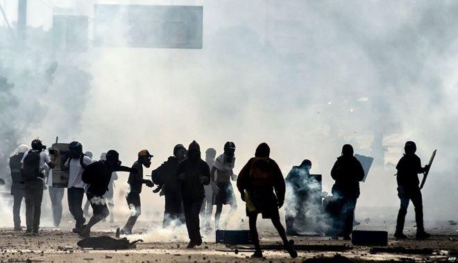 Антиправительственные демонстранты и полиция окружены слезоточивым газом во время демонстрации, которая перекрыла шоссе Франсиско Фахардо в Каракасе в мае 2017 года