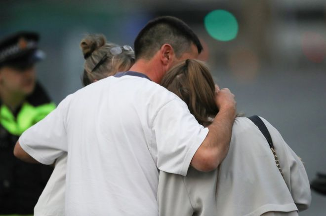 A man embraces a woman and a teenager as he collects them from the Park Inn Hotel where they were given refuge after last nights explosion at the Manchester Arena on 23 May 2017 in Manchester, England.