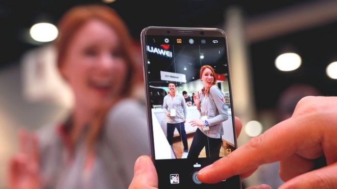 A Huawei phone being used to take a picture of a woman