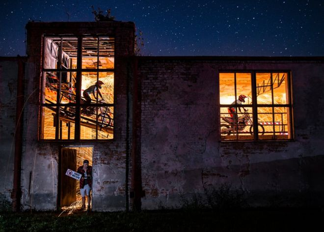 Cyclists through a warehouse window