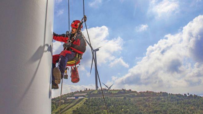 Un técnico trabajando sobre una turbina de viento