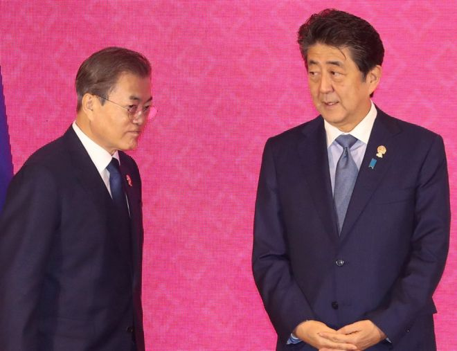 South Korean President Moon Jae-in walks past Japanese Prime Minister Shinzo Abe in Bangkok, Thailand, November 4, 2019