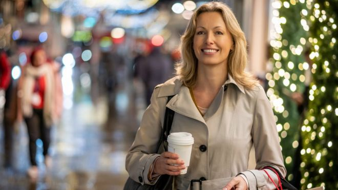 Woman with a takeaway coffee Christmas shopping