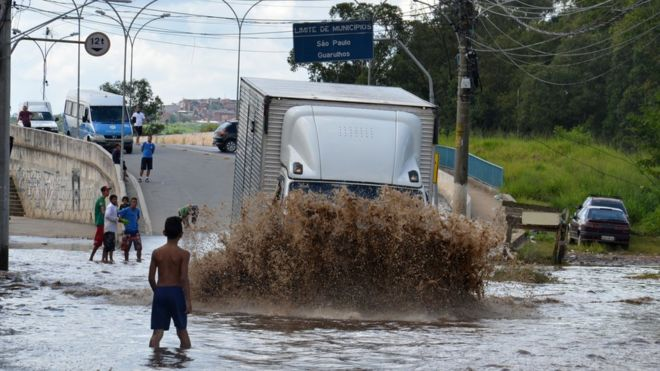 Menino observa caminhão passando por enchente próximo à ponte da Vila Any