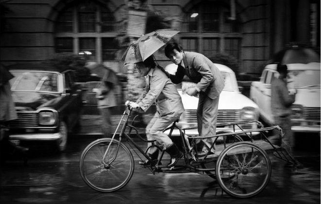 三轮车上的打伞男子