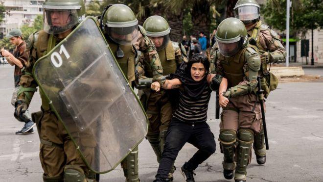carabineros se llevan a una manifestante