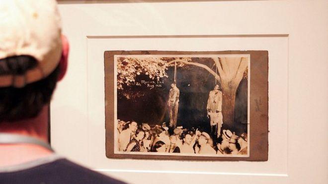 Em uma exposição, homem observa fotografia de linchamento nos Estados Unidos