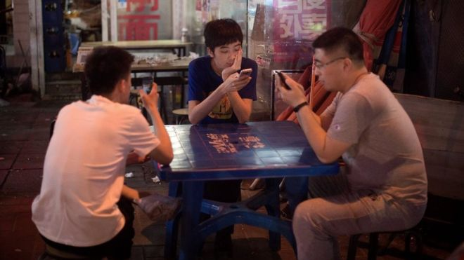 Three men sitting at a table staring at their phones